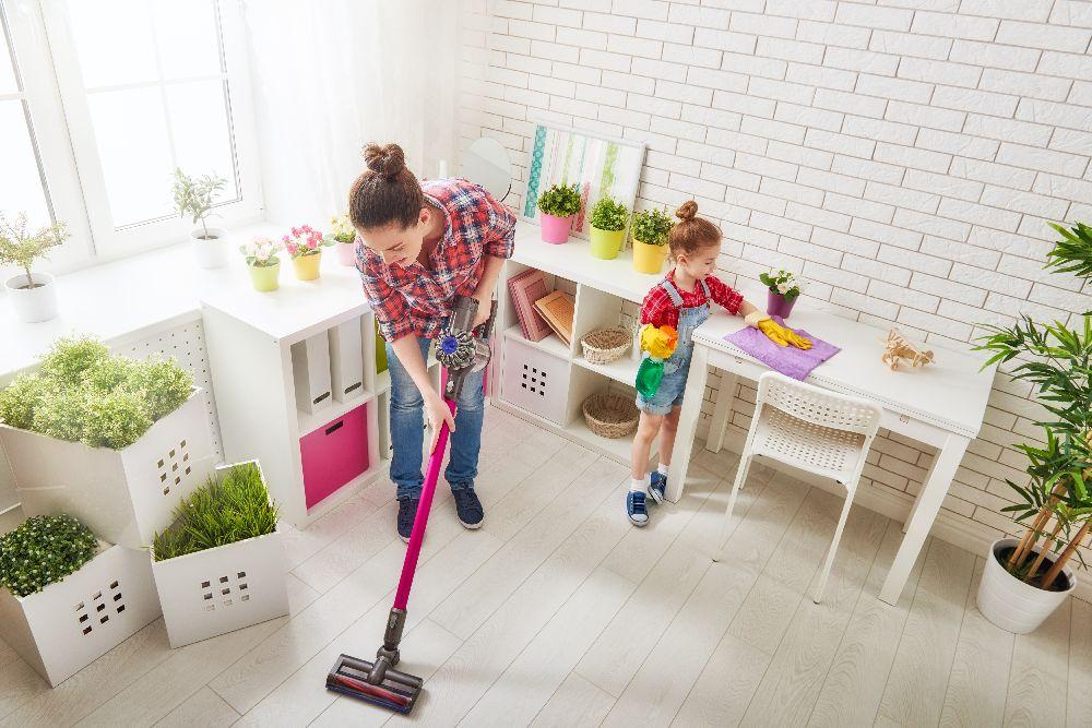 Frau staubsaugt in Wohnung