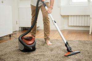 Mann saugt auf Teppich mit Staubsauger